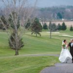 Happy Wedding couple walking along golf green